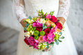 Bride holding rose pink wedding bouquet of roses and love flowers Royalty Free Stock Photo