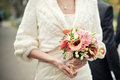 Bride holding wedding bouquet from orange calla lilies and freesia selective focus on a Stock Photo