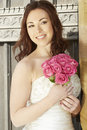 Bride holding a wedding bouquet of pink roses female in church door smiling Stock Image