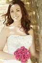 Bride holding a wedding bouquet of pink roses female at church smiling Stock Photos