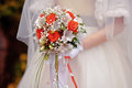 Bride holding a wedding bouquet with white and red flowers Royalty Free Stock Photo