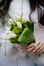 Bride holding wedding bouquet from white tulipes and golden dais daisies selective focus on a Royalty Free Stock Images