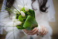 Bride holding wedding bouquet from white tulipes and golden dais daisies selective focus on a Royalty Free Stock Photography