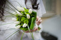 Bride holding wedding bouquet from white tulipes and golden daisies selective focus on a Stock Photography