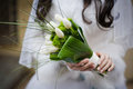 Bride holding wedding bouquet from white tulipes and golden daisies selective focus on a Royalty Free Stock Photography