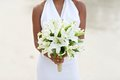 Bride holding white lily flower wedding bouquet