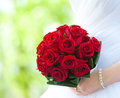 Bride holds bouquet of red roses summer green background Stock Photography