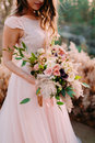 A bride holds rustic wedding bouquet consisting of different flowers. Decoration Artwork