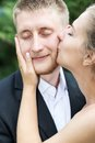 Bride kisses groom on the cheek tenderly closeup Stock Images