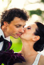 Bride kissing groom outdoors in park Royalty Free Stock Photos