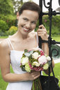 Bride leaning on garden gate holding bouquet beautiful young Royalty Free Stock Photography