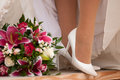 Bride legs with boquet s in white shoes Royalty Free Stock Photos