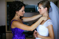 Bride looks funny while bridesmaid adjusts an earring Royalty Free Stock Photo