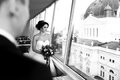 Bride looks thoughtful out of the window at cityscape a Royalty Free Stock Image