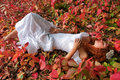 Bride lying among red leave Royalty Free Stock Photo