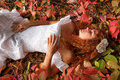 Bride lying among red leaves
