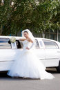 A bride near the long white wedding car Royalty Free Stock Photography