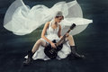 Bride playing wedding rock guitar in dress with veil over artistic dark background in brutal boots Royalty Free Stock Photos