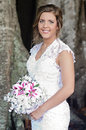 Bride portrait outdoors a three quarter of a beautiful smiling standing under a banyan tree holding bouquet Royalty Free Stock Photo