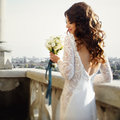 Bride poses back with lily bouquet with cityscape on the background Royalty Free Stock Photo