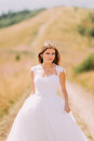 Bride posing on the golden autumn field with a marvelous hill landscape behind her Royalty Free Stock Photo