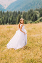 Bride posing on the golden autumn field with marvelous mountain landscape behind her Royalty Free Stock Photo