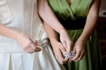 Bride is putting on the bracelet stock photo her friend in green dress helping her Stock Image