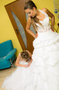 Bride putting on wedding gown Stock Photo
