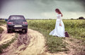 Bride on the rural road with an old suitcase Stock Images