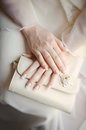 Bride s arms with manicure holding a wedding purse Stock Photography