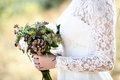The bride s bouquet from cones and cotton close up in hands of lace dress forest backdrop Stock Photos