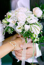 Bride's and groom's hands with wedding bouquet Stock Photos