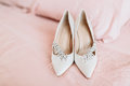 Bride`s shoes for the wedding day on bed sheet Royalty Free Stock Photo