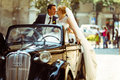 Bride's veil hangs down while she kisses a groom sitting on a re Royalty Free Stock Photo