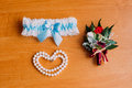 Bride's wedding accessories, white garter with blue ribbon, bracelet of pearls and cute little boutonniere. Preparing Royalty Free Stock Photo