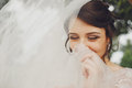 Bride shines standing with closed eyes and hiding her smile behi Royalty Free Stock Photo