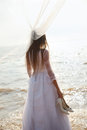 Bride with shoes is standing on the beach and holding her Royalty Free Stock Images