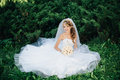 Bride sitting on green grass at park Royalty Free Stock Photo