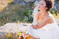 Bride sitting on the stone Stock Photography