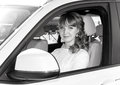 Bride sitting in white car, monochrome photo Royalty Free Stock Photo