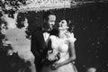 Bride smiles standing in groom`s hugs behind a garden lake Royalty Free Stock Photo
