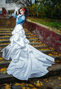 Bride on stairs beautiful in magnificent dress stands alone in autumn day Royalty Free Stock Image