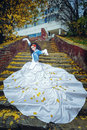 Bride on stairs beautiful in magnificent dress stands alone in autumn day Royalty Free Stock Images