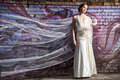 Bride standing near colorful wall with flying veil portrait of beautiful Stock Photo