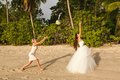 Bride throwing bouquet for girls to catch seychelles Royalty Free Stock Photography