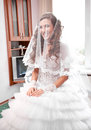Bride under white veil sitting in appartment beautiful Royalty Free Stock Image