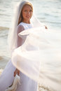Bride with the veil is standing on beach and holding her flying Royalty Free Stock Image