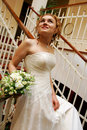 Bride walking downstairs with bouquet Royalty Free Stock Photos