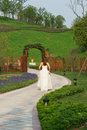 Bride walking in park with wooden gate Royalty Free Stock Photography