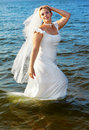 Bride walking in sea Stock Photo